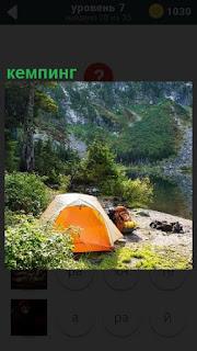 В горах на поляне находится палатка, кемпинг желтого цвета около кустов