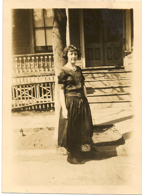 Photo of unidentified woman, probably a Dixon, standing at the curb in front of a house. Between 1920-1940. Printed in Elizabeth, NJ at Graham & McCloskey.