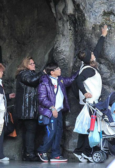 Tocando a pedra abençoada da gruta