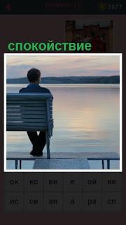 на скамейке перед водоемом сидит мужчина