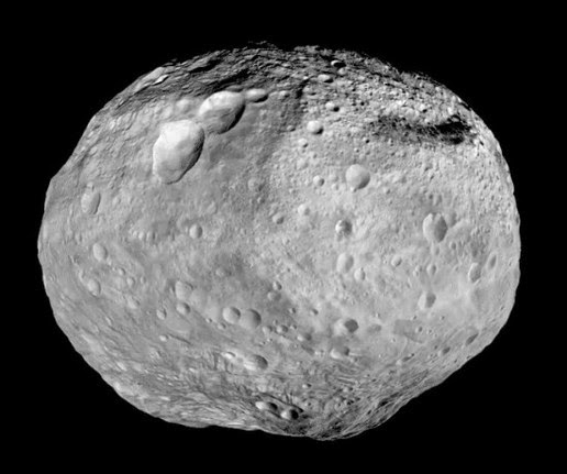 "Dawn studying Vesta from July 2011 until September 2012. A towering mountain at the south pole of Vesta - it more than twice the height of Mount Everest - look at the bottom of the image. A series of three craters, known as the ""snowman"" can be seen at the top left."