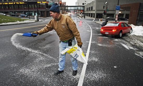 Homem jogando sal no asfalto