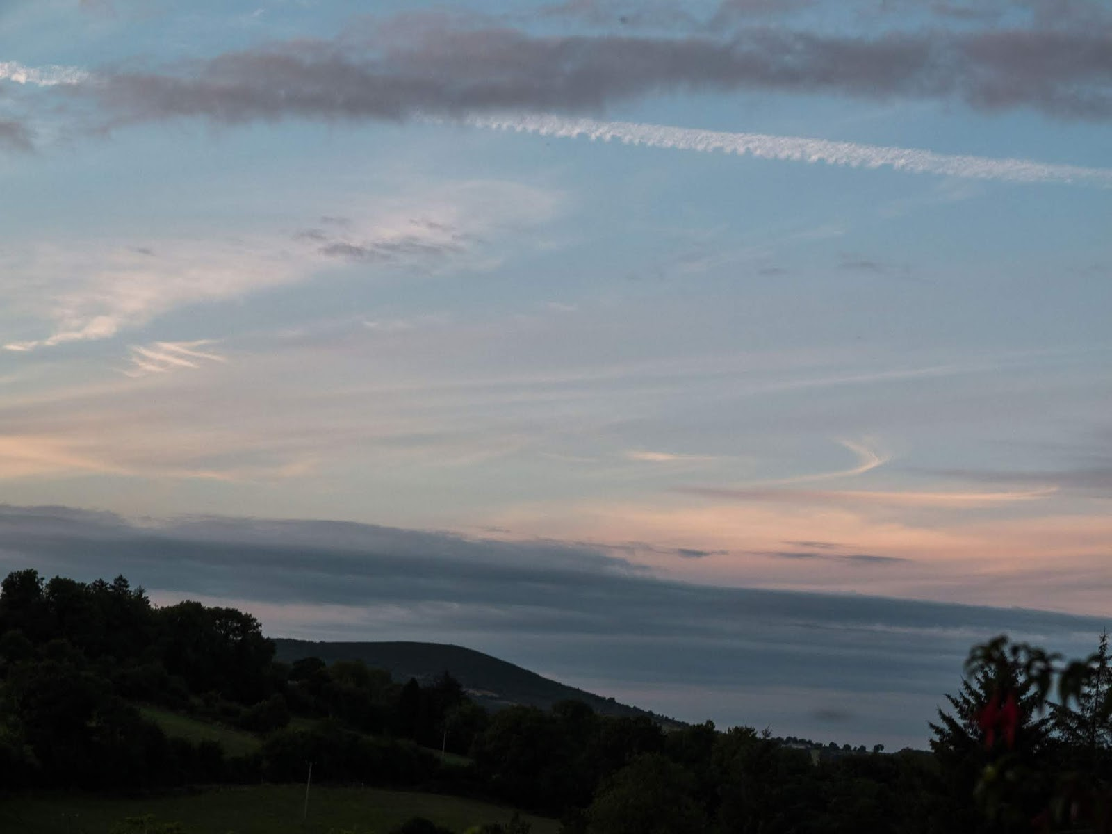 Light blue pastel sunset sky with scattered clouds over a hillside in North County Cork.