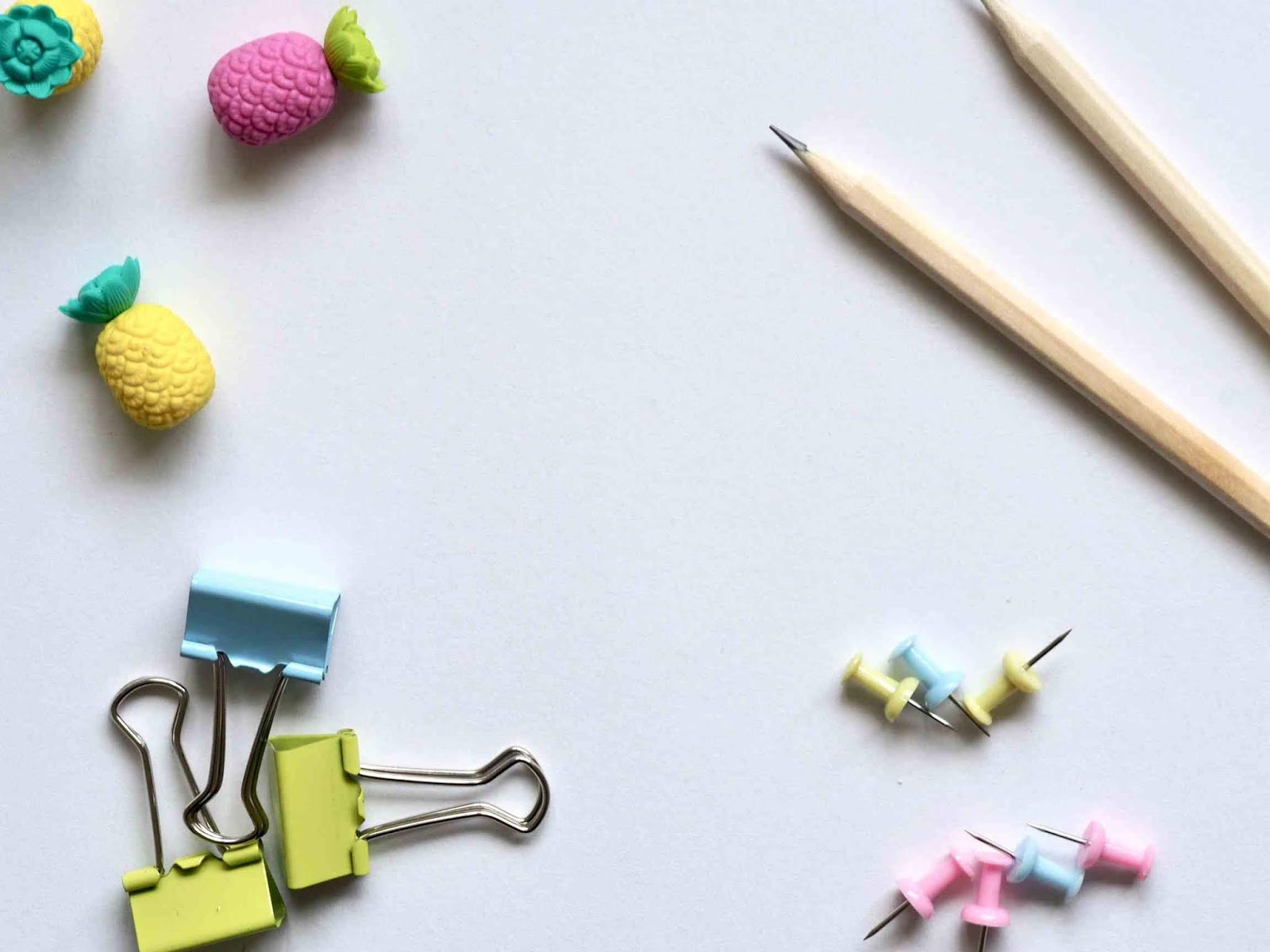 A photo of two pencils, pins, three paper clips, and magnets in bright colors