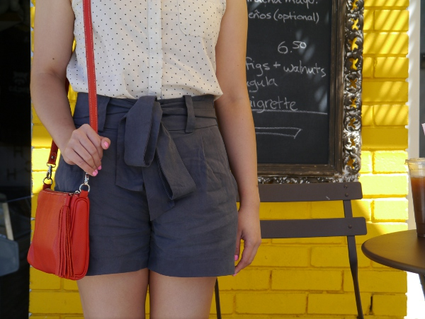 A Swiss dot sleeveless blouse, worn with neon pink nails, a red leather shoulder bag, and gray tie-waist shorts.