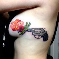 Tatuajes femeninos en las costillas revolver flores