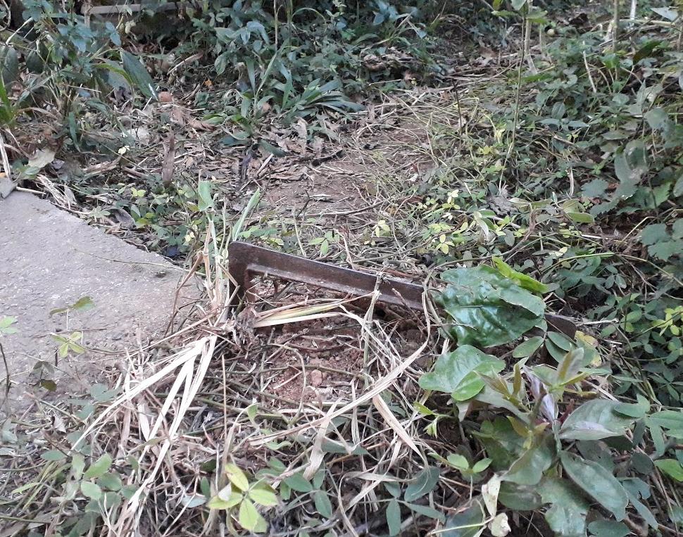 A ferramenta metálica no quintal do Sr. Mitsiotis era usada antigamente pelos moradores para limpar as botas sujas de barro em um bairro Jaraguá que não tinha asfato