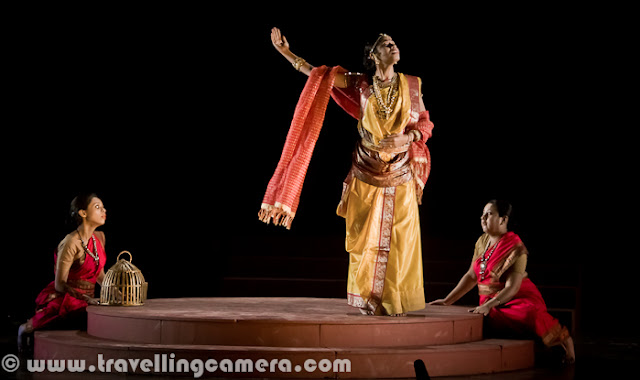 Here are some more pictures from the play Chandalika. To give you some context of the play, it was written by the legendary Rabindranath Tagore and it is the tale of Prakriti, an untouchable girl forced to live on the periphery of society as 'chandalika'. No one want to play with her, people keep distance from her but at times interact with her for their personal benefits. The play is based on a story from a Buddhist text. Play starts with some dialogs by Usha Ganguli where she describes the situation of her region without water and how people are crying for water. Usha is playing main role in this play. She has a daughter and both of them are treated badly by higher society. At the same time, she helps the local kingdom by helping in various problems like water scarcity. Setting and expressions are two powerful tools used to assist dialogs and action in drama for conveying important information to the viewers. Through these tools a lot can be shown without actually being said. For example, firewood, earthen pots etc. show a rural setting and may also indicate that the play is set in past. Everything cannot be expressed in words because then  the play will be much too lengthy, boring and unintelligent.Interactions between characters, their expressions and their actions often hide a subtext that is very interesting to unearth. For example, in this scene, can you make out what the character is feeling of thinking without actually knowing what is going on? One can easily assume that the character is not unhappy and may even be pleased about things. I can also see a hint of dreaminess in the eyes and may be lost in thoughts about her beloved. But then that is my interpretation and how close it is to the actual emotions being portrayed by the character depends upon the character's acting skills and my ability to read expressions. The expressions here are more of defiance and questioning. But then again that is my interpretation and I can be wrong. Another thing you'd want to note is the attire and the make-up. All efforts are made to keep them true to the situation, the period, and the story. For example, here the dhotis and the lathis indicate that the setting is rural and the expressions of various characters indicate their emotions. For example, the person who is chained is reluctant to go where he is being led and the person in the red dhoti seems to be pleased with himself and takes pleasure in the predicament the chained person is in. Flowers, dances, audience, claps indicate celebrations of either a festival or an event. Some people are wearing garlands and this may indicate their special place in the society. Graceful dance moves and melodious singing are all often a part of dramas and I am amazed by the number of talents most of the stage artists hide within themselves. Almost all of them sing well and dance well along with obviously acting well. One-on-one interactions are some of the most interesting interactions in a play. They reveal more about a character and her relationships with other characters than any other interaction in a play. These are usually more difficult to carry out because the audience is focussed upon the characters involved. These are more challenging for the actors than for the directors.Multiple characters interactions are more challenging for the playwriter and for the director because it requires exceptional skills to craft such scenes. Colors and body languages tell stories of themselves. The next time you go to watch a play, try to keep an eye on these things and you will be amazed at what you will discover.Presence of objects such as cages can be symbolism that you had never suspected. If you observe these things, you will add layers to your play-watching experience. For example, here it is clear that the woman in the centre is someone who has power over the other two. The cage represents imprisonment or curtailment of freedom. The attire of this woman indicates affluence and her demeaner indicates power and even royalty. Is there anything else you can make out? Feel free to leave a comment if you can. The body language of the characters here indicates a mother-daughter relationship. And the leaves and the leaves indicate some sort of a ritual or religious practice. The clothes of these two characters are much simpler. The characters are not affluent but aren't poor either. Let me know if you can read more into these pictures. I would love to know. Please feel free to leave a comment.