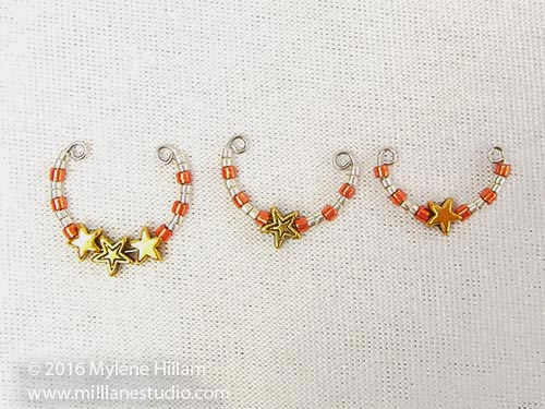 Three different sized memory wire coils strung with gold stars and silver and copper seed beadsbeads