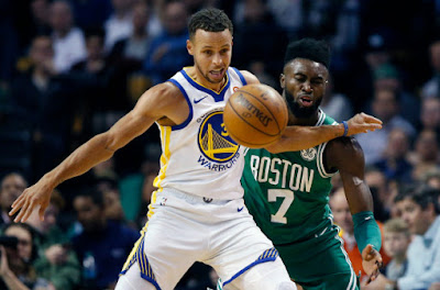 Stephen Curry uses his body to protect the ball against Jaylen Brown