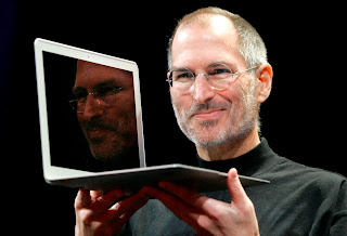 Steve Jobs holding a Macbook