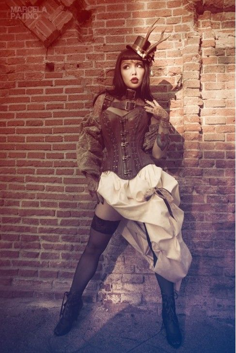 women's steampunk clothing includes brown leather corset, white bustle skirt and fascinator with top hat and real animal antlers.