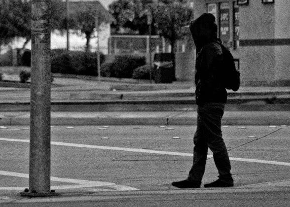 boy walking alone on road -#main