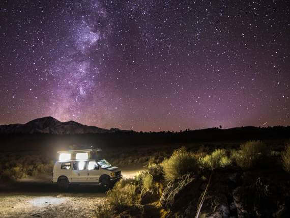 van in the desert under the milky way