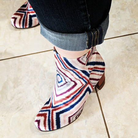 image of my feet in white velvet ankle boots with a red and blue geometric pattern