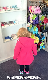 Toddler browsing the racks of shoes