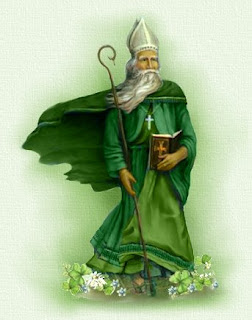St. Patrick in flowing green robes and a tall white hat carrying a bible and a staff. There are shamrocks with white blooms at this feet.