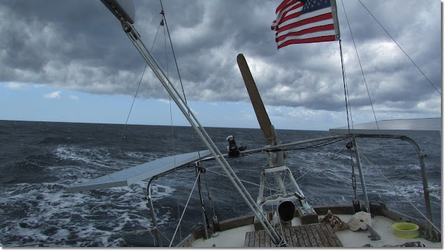 The stern of a sailboat crashing through rough seas trying to outrun the encroaching storm.