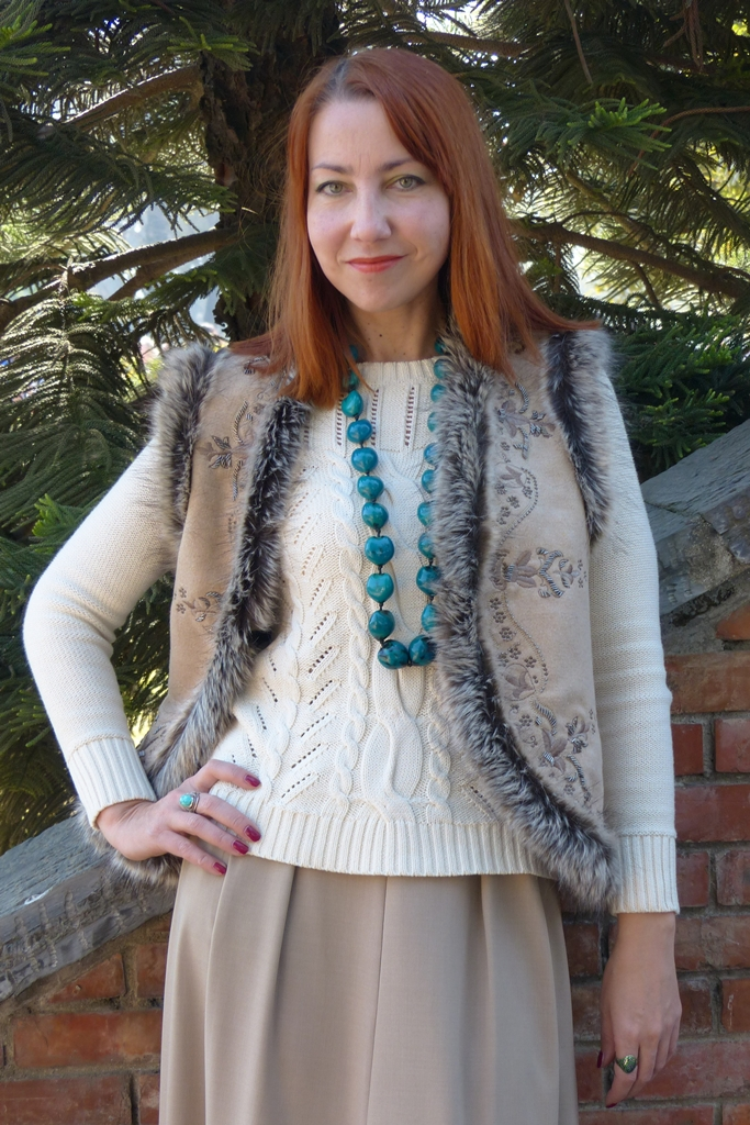 Fur trimmed embroidered vest worn over cotton sweater with large beads necklace