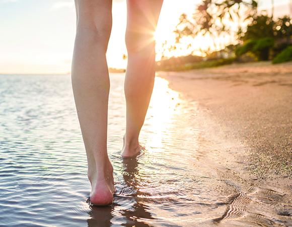 Mulher caminhando na beira da praia