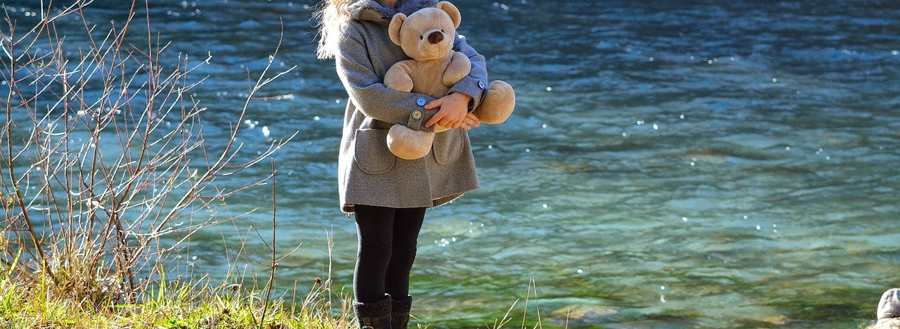 Kind steht an einem Fluss