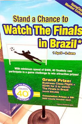 """Stand a chance to watch the finals in Brazil"", invites a standee from Courts. The picture of a footballer with a football and the goal posts make the World Cup allusion unmistakeable. There is quite a lot of yellow and green in he image as well but it's not quite the Brazilian green or yellow."