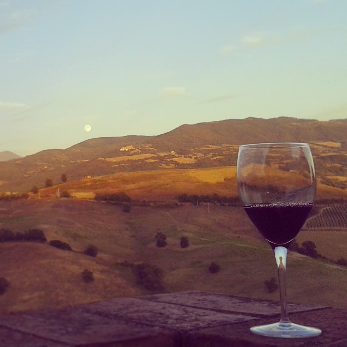 A glass of Montecucco wine, full moon and the view from Cinigiano towards Castiglioncello Bandini