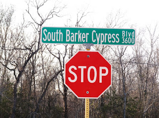 South Barker Cypress Blvd road name sign with stop sign