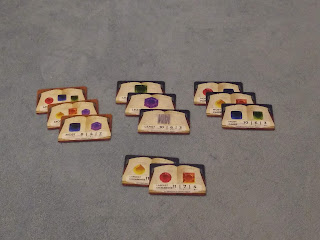 Three stacks of three and one stack of two cards. Each card has one or more colour (or blank sword tiles icons) and a rule for how they are scored on a background that looks like an open book.
