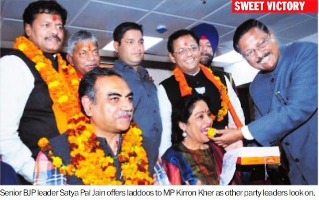 Senior BJP leader Satya Pal Jain offers laddoos to MP Kirron Kher as other party leaders look on