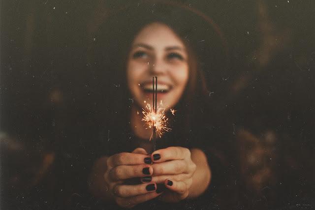 Chica con sombrero sonriendo feliz, con chispas, estrellitas riendo de felicidad