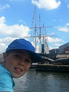 Boy leaning over boat side with ships in the background
