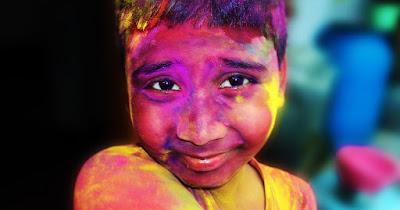 Niño en el festival de Holi en India. Celebran la primavera.