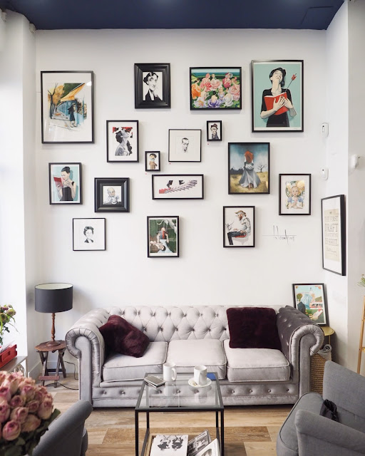 Sofá chester gris frente a una pared con ilustraciones de Fernando Vicente