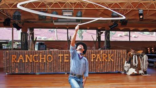 Cowboy lassoing in front of a sign that says 'Rancho Texas'