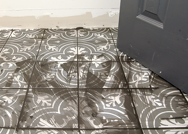 Grouting patterned charcoal gray mosaic tile