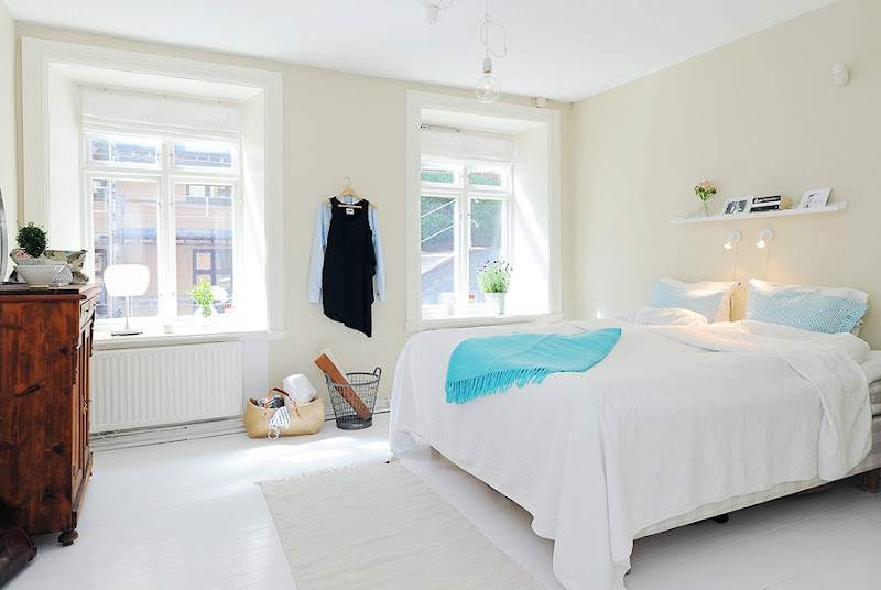White minimalist bedroom with turquoise throw, blue and white patterned pillows, sea grass rug at the foot of the bed and wood chest of drawers