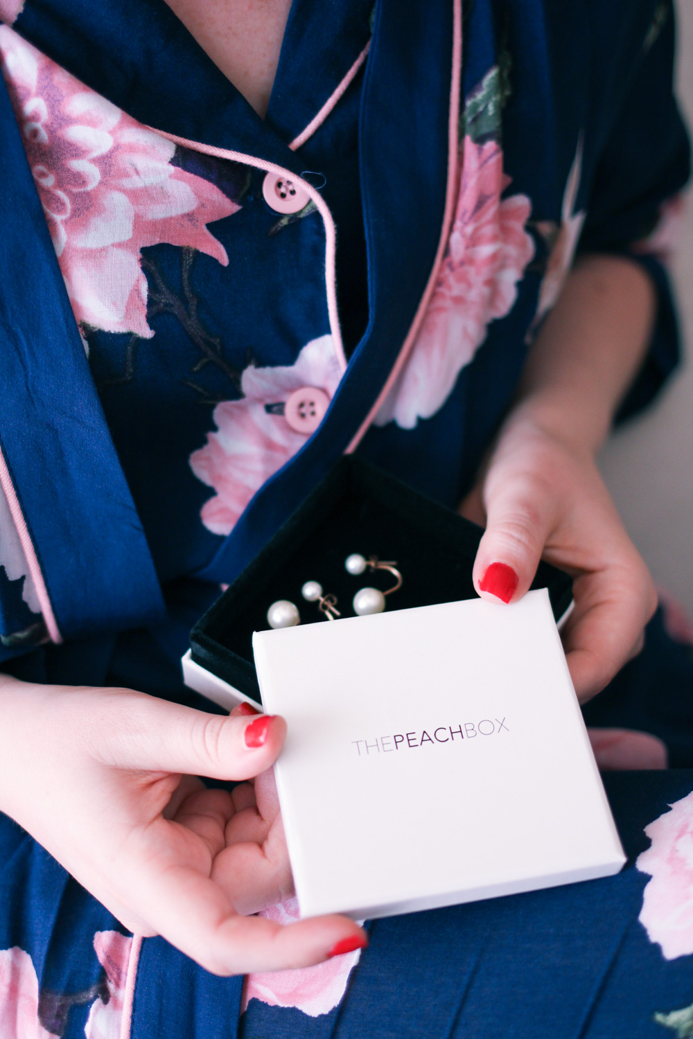 @findingfemme wears The Peach Box pearl earrings and Target floral pyjamas.