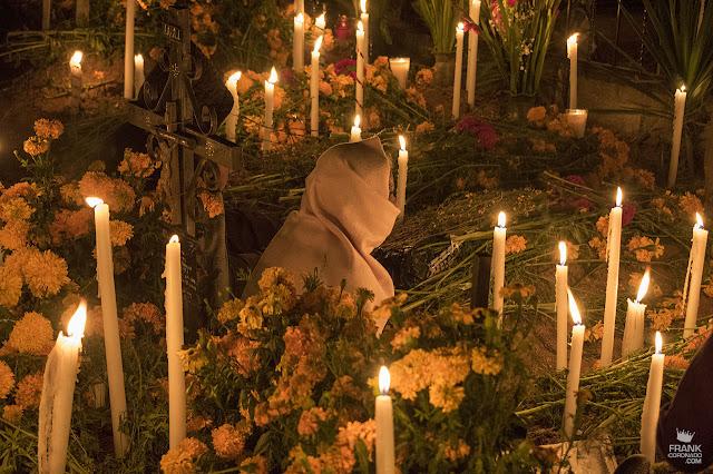 Mujer con velas en panteón el día de muertos en Oaxaca