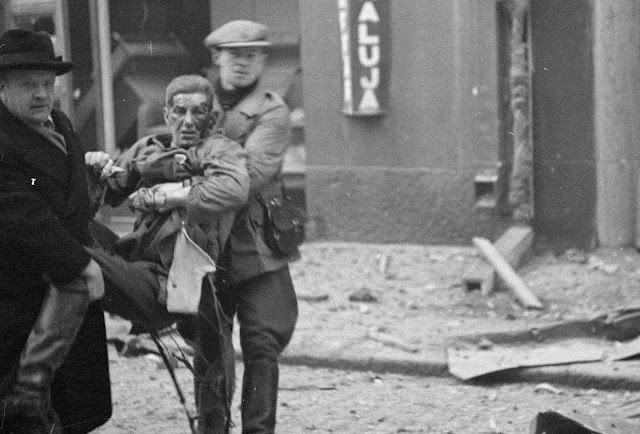 A wounded man is carried away after bombardment of a civilian area.