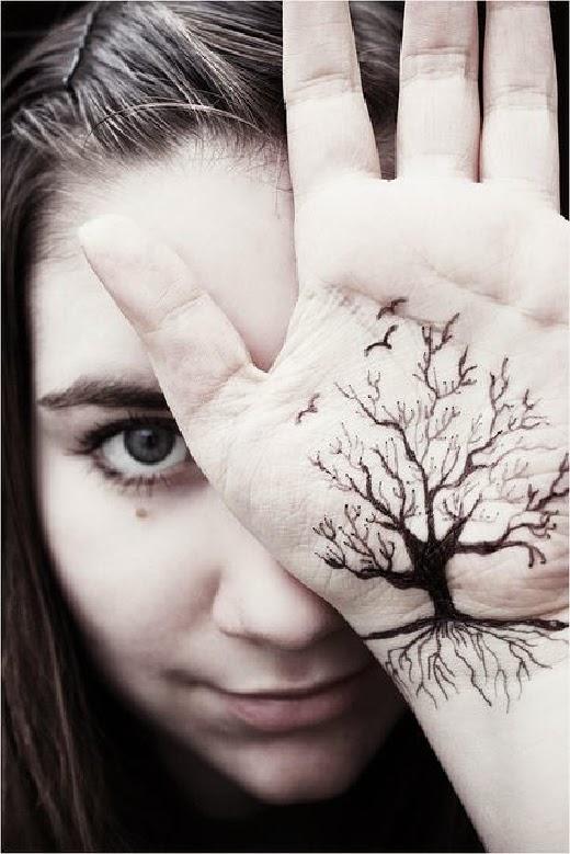 vemos a una chica muy joven con un tatuaje en la palma de la mano el tattoo de la silueta un arbol