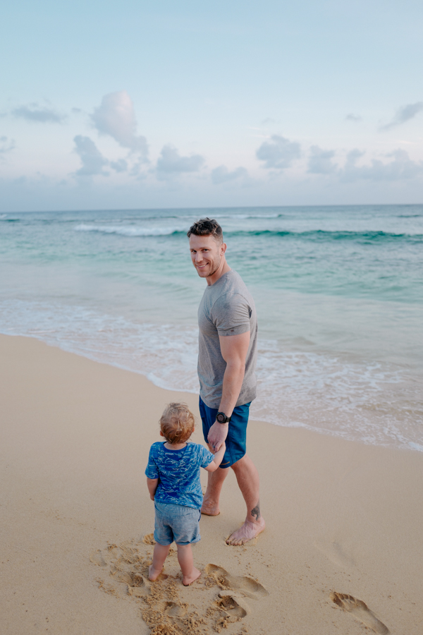 father-toddler holding hands on the beach