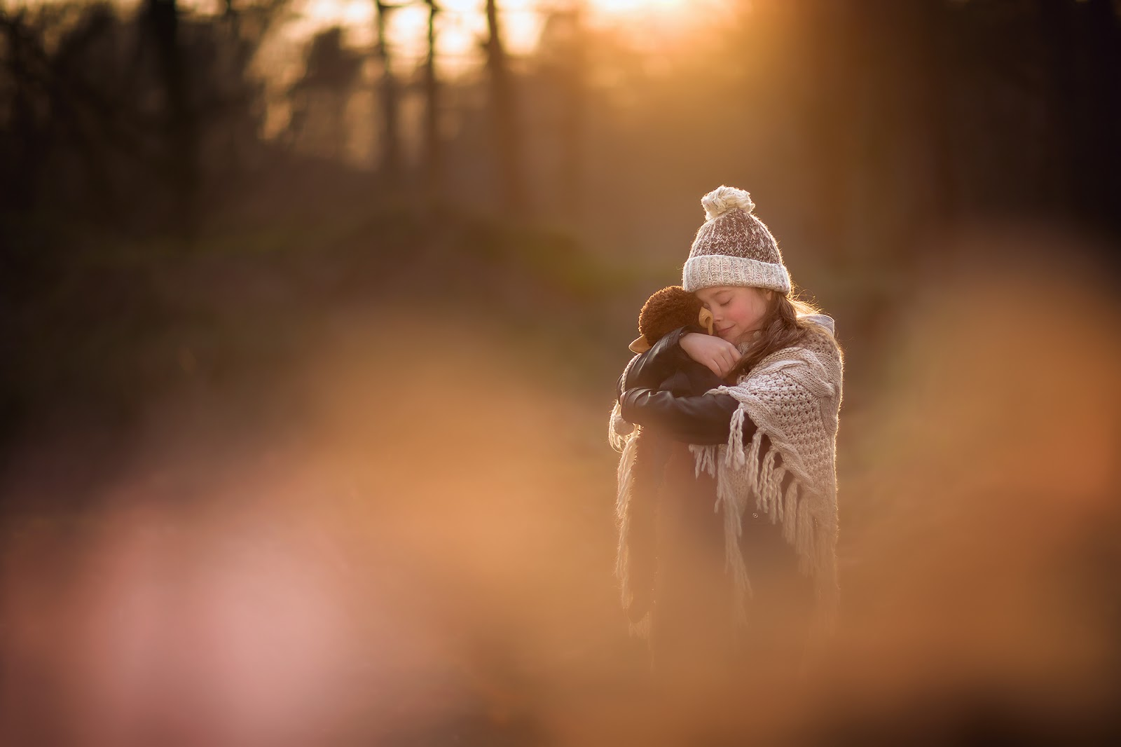 Canon color image of a little girl with a hat in winter and her stuffed animal monkey during sunset by Willie Kers