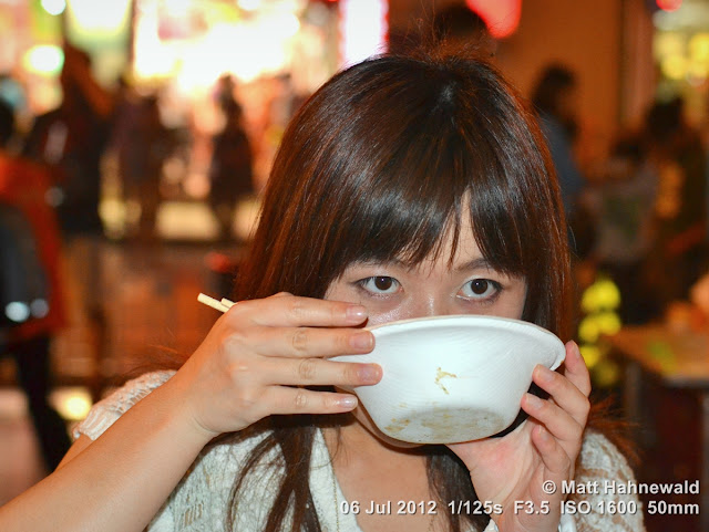 China; Beijing; Donghuamen Night Market; Chinese woman slurping noodles; Chinese food delicacies; chop sticks; Matt Hahnewald; Facing the World; portrait; street portrait; food; noodles; noodle soup; night; bokeh; travel; travel destination; tourism
