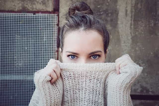 woman hiding face in sweater