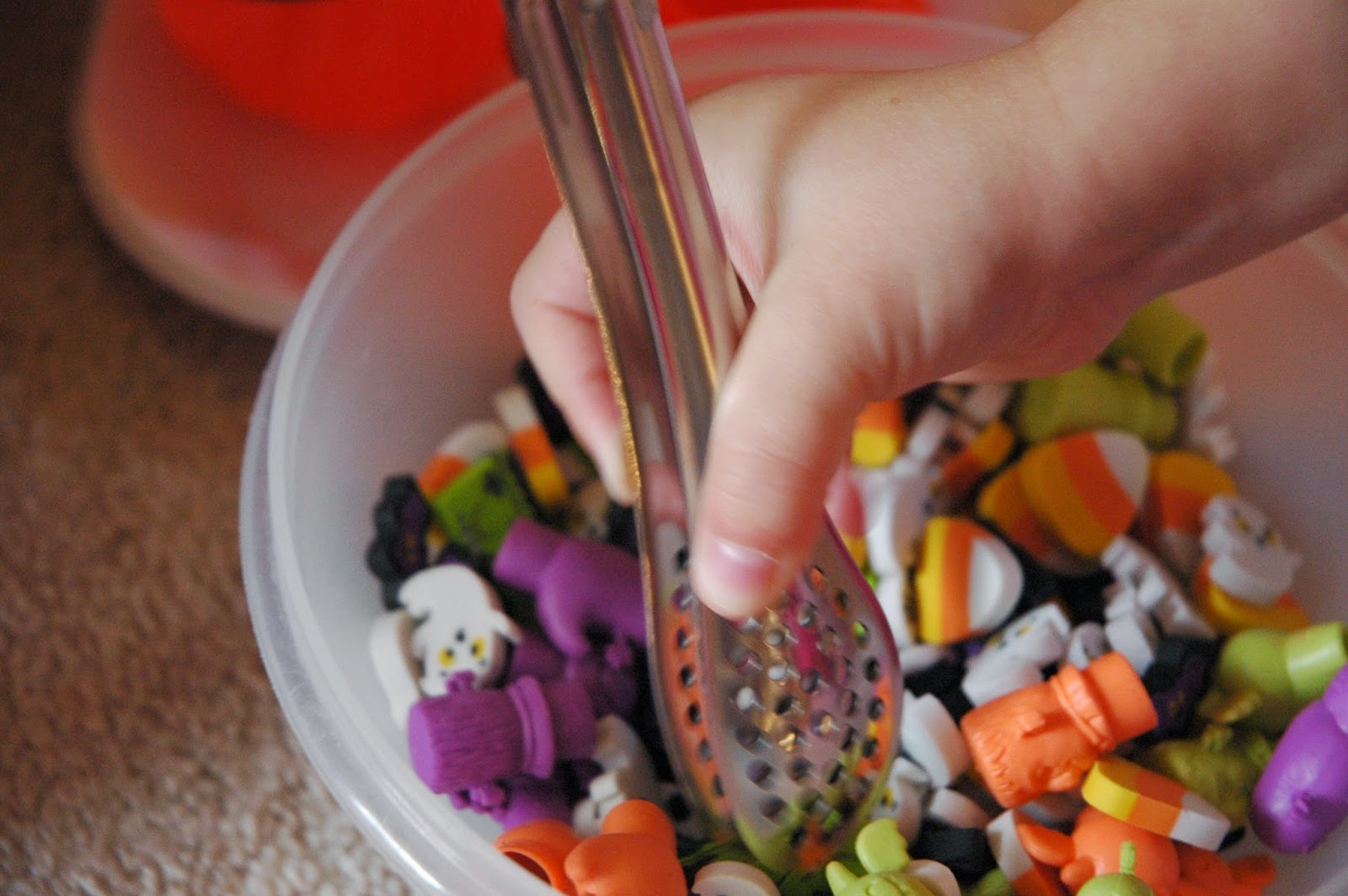 Using tongs to sort erasers as fine motor activity
