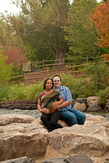 a happy couple posed for a maternity session on a river in Colorado in autumn