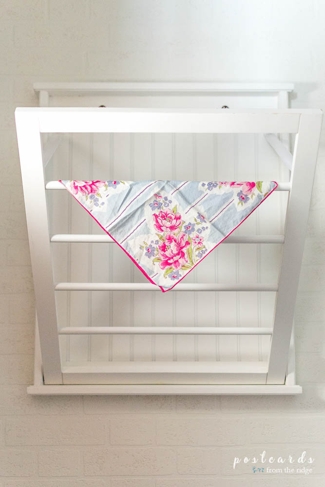 This low budget laundry room makeover is darling. Love the drying rack and vintage hankie!