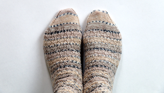 Top View of Hand Knit Wool Socks in Beige and Gray Self-Striping Yarn