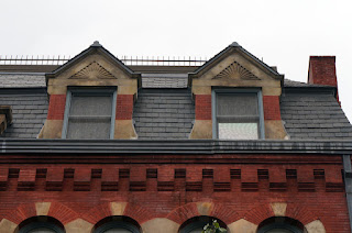 Dormers in mansard roof of old, historic red brick building.